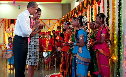 US President Barack Obama and First Lady Michelle Obama greet young dancers at a Diwali lamp lighting in Mumbai